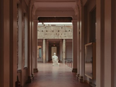 Empty museum hallway with a marble statue at the end